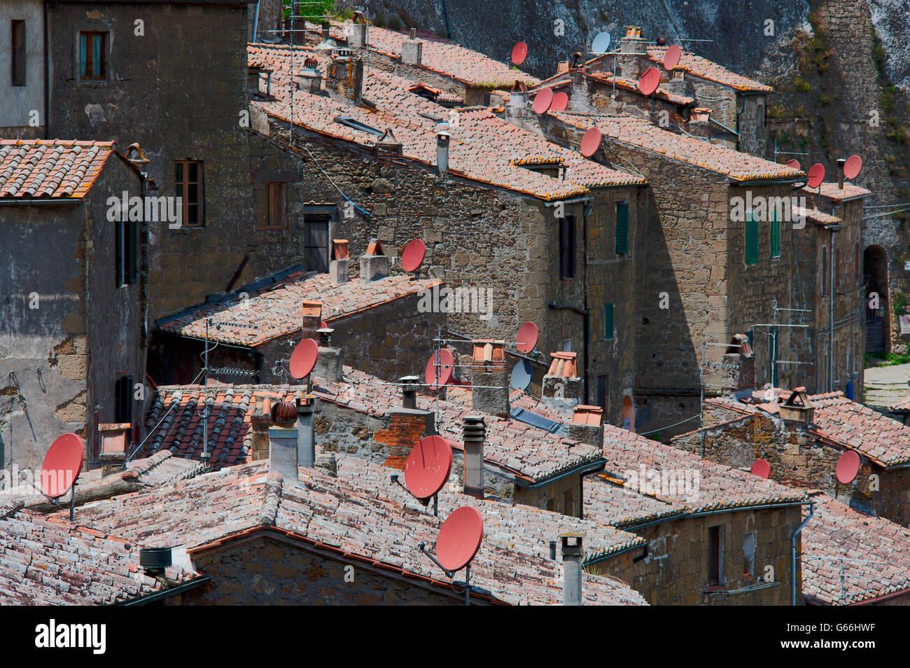 Satellite Tv dishes on terracotta tiled roofs in Sovana - Stock Image