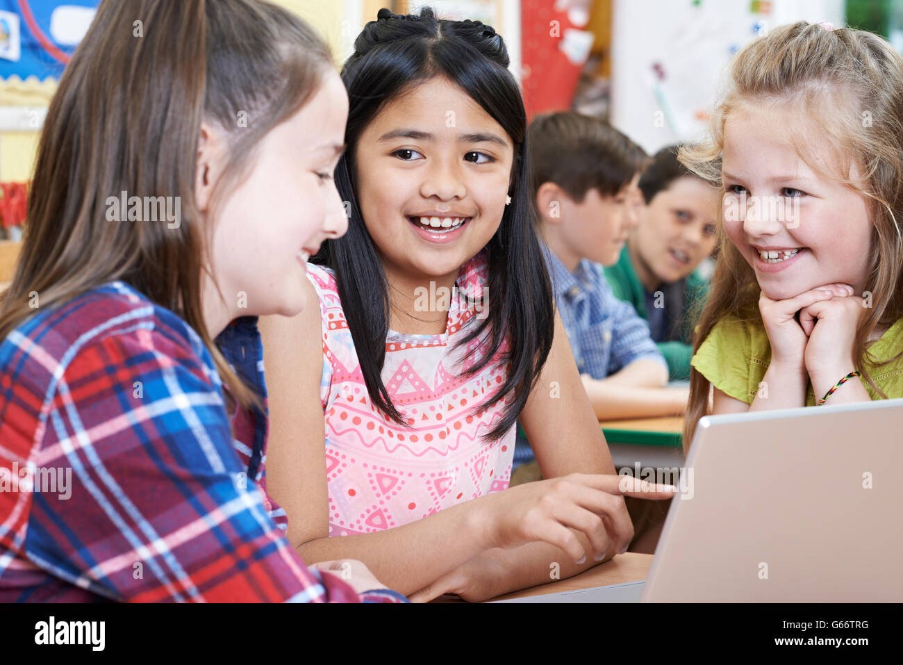 Group Of Elementary School Children Working Together In Computer Class - Stock Image