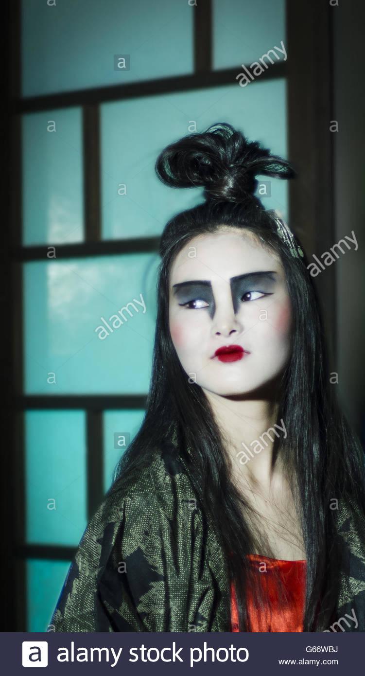 Beautiful young Japanese woman wearing red dress and kimono. - Stock Image