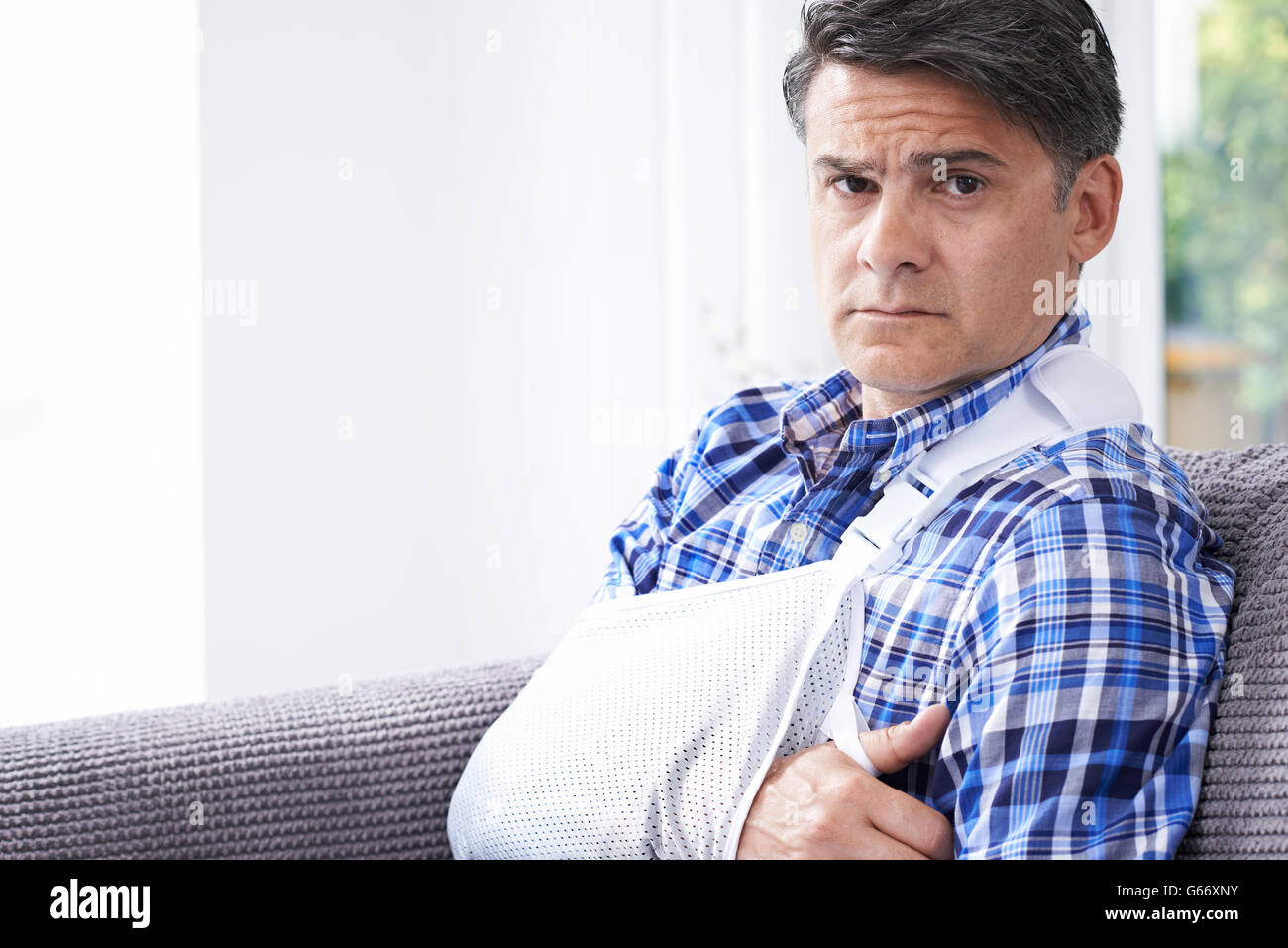 Portrait Of Mature Man With Arm In Sling At Home - Stock Image