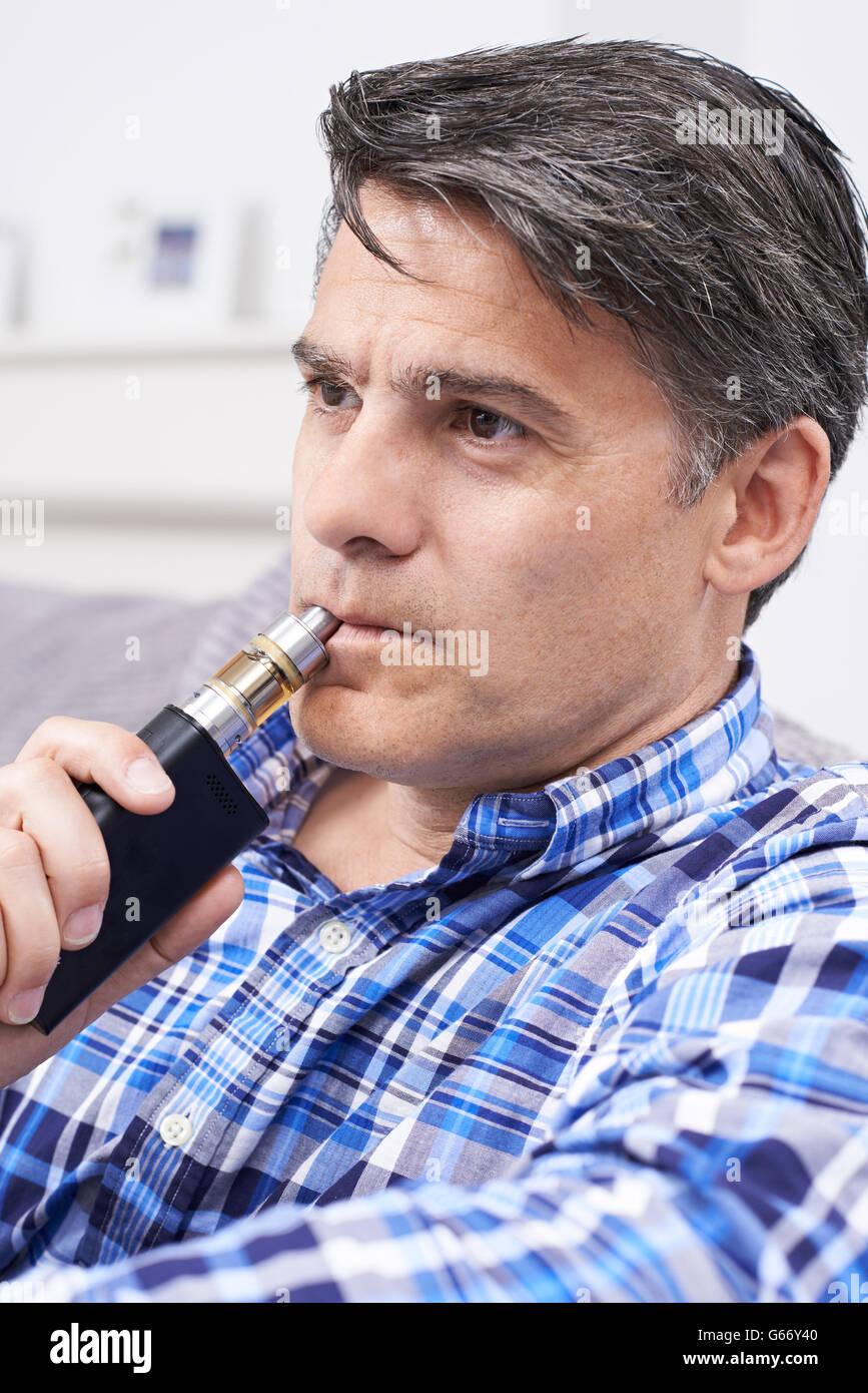 Mature Man Using Vapourizer As Smoking Alternative - Stock Image