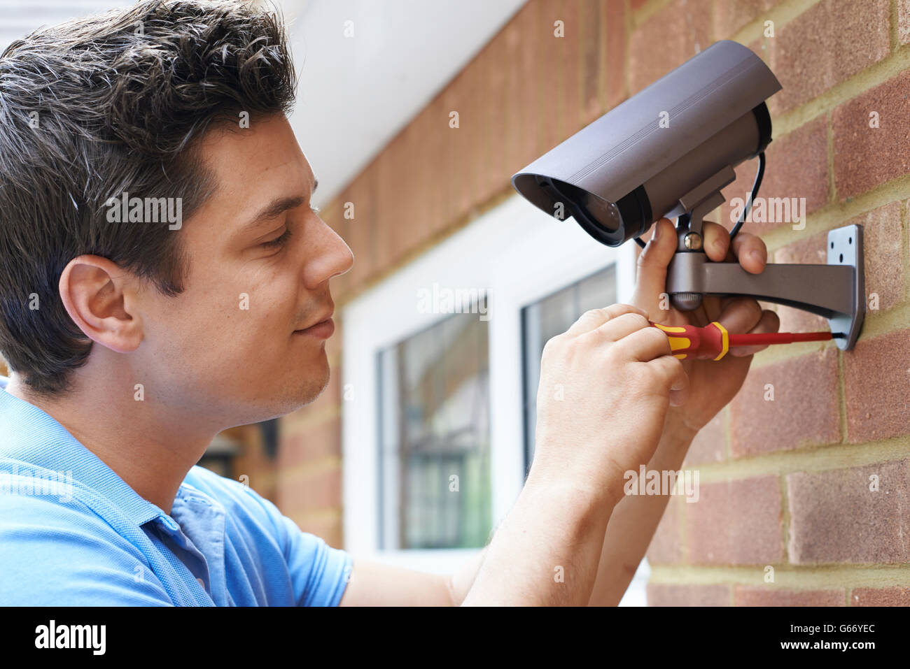 Security Consultant Fitting Security Camera To House Wall - Stock Image