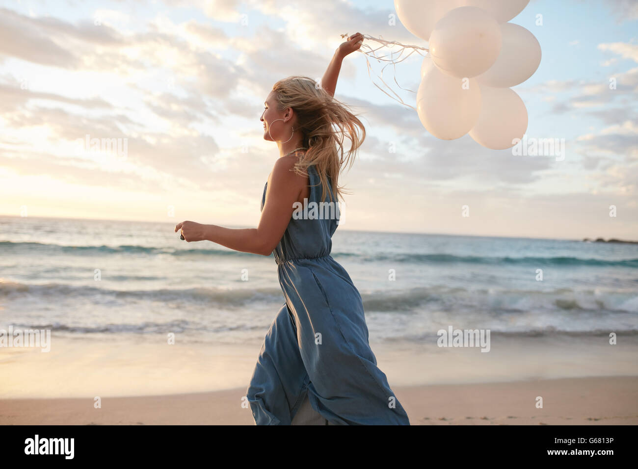 Side view shot of beautiful young woman running on the beach holding balloons. Female running on the sea shore and - Stock Image