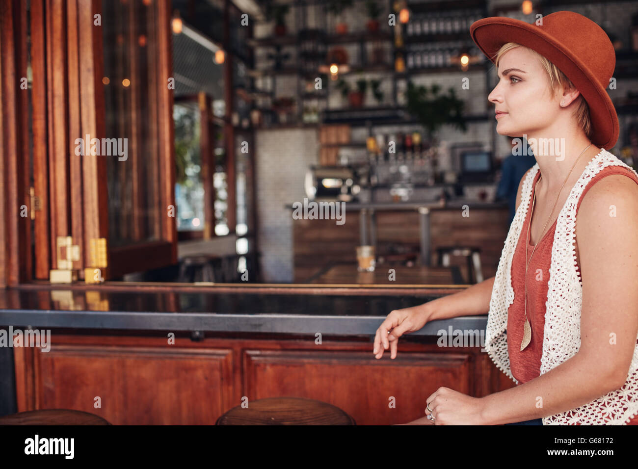 Side view of beautiful young caucasian woman sitting at bar counter and looking away. She is wearing hat waiting - Stock Image