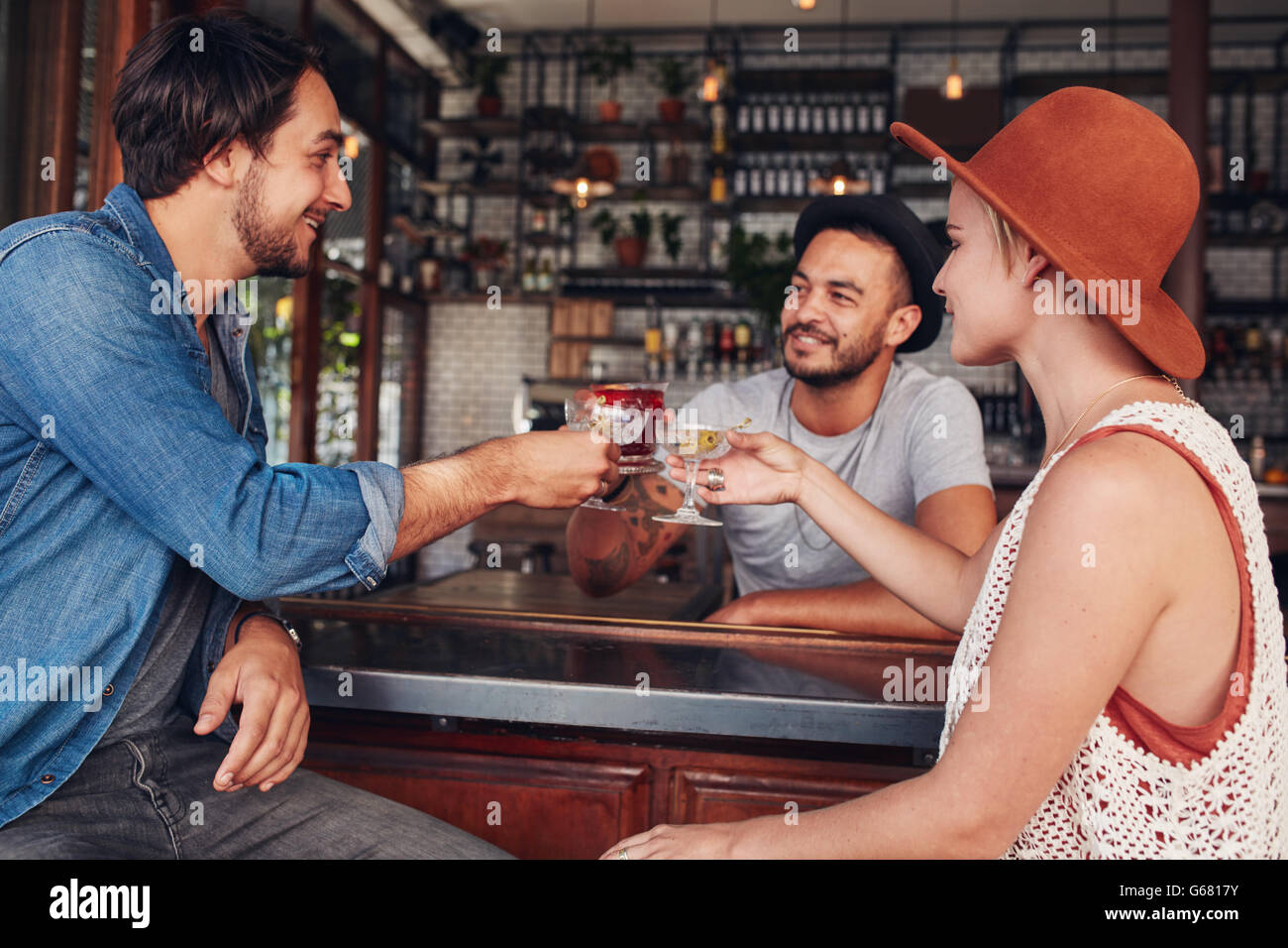 Three young people toasting drinks at cafe. Young men and woman having a glass of drink at bar. - Stock Image