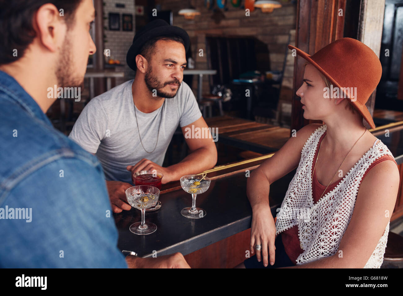 Group of young friends sitting and talking at a cafe. Young men and women meeting in a coffee shop and discussing. - Stock Image