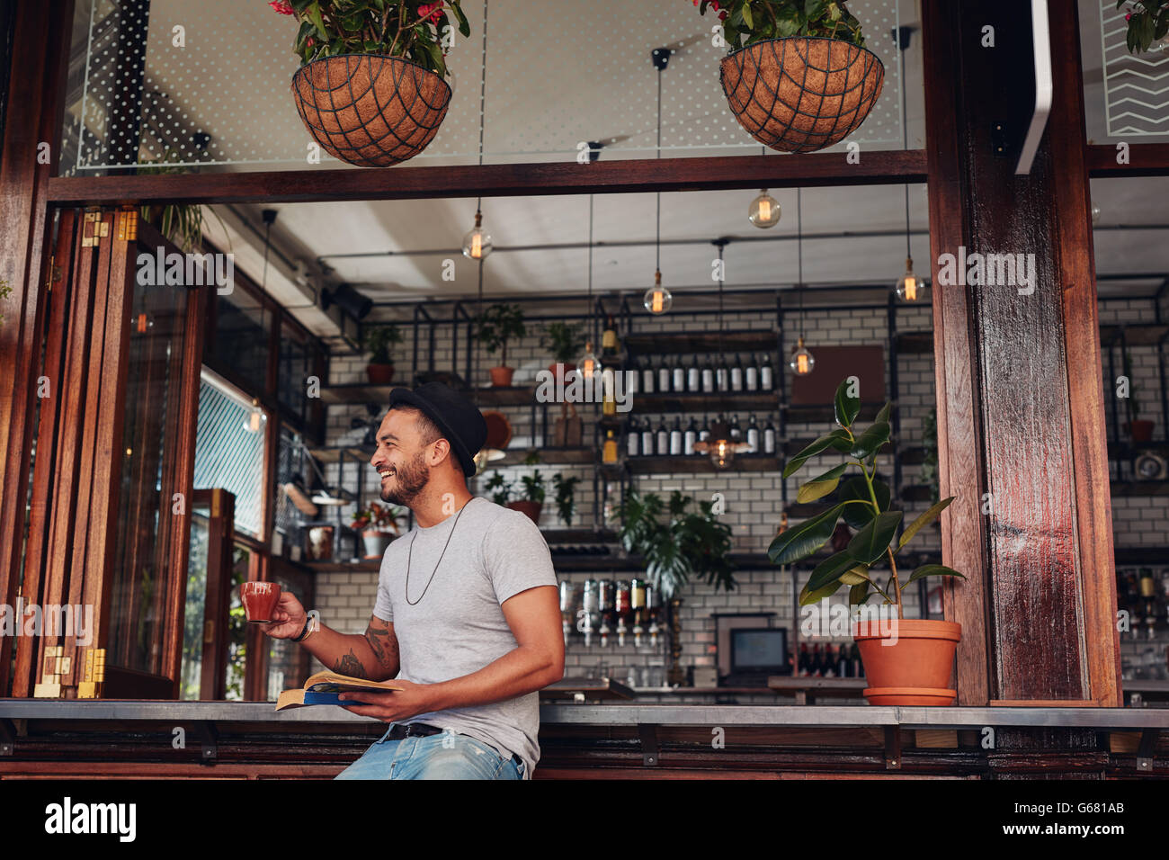 Happy young man drinking coffee and reading book at a cafe. Young guy enjoying a cup of coffee while reading a novel. - Stock Image