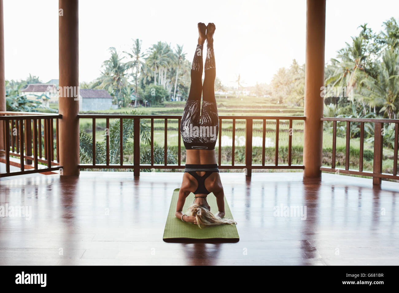 Rear view shot of fitness woman doing the headstand yoga in healthy club. Healthy female doing headstand asana. - Stock Image