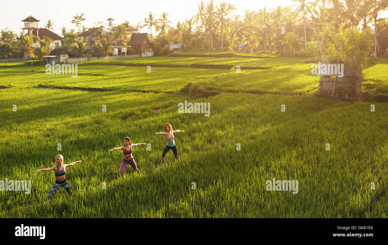 Fitness woman doing yoga in farm outdoors. Yoga class in farm lands. - Stock Image