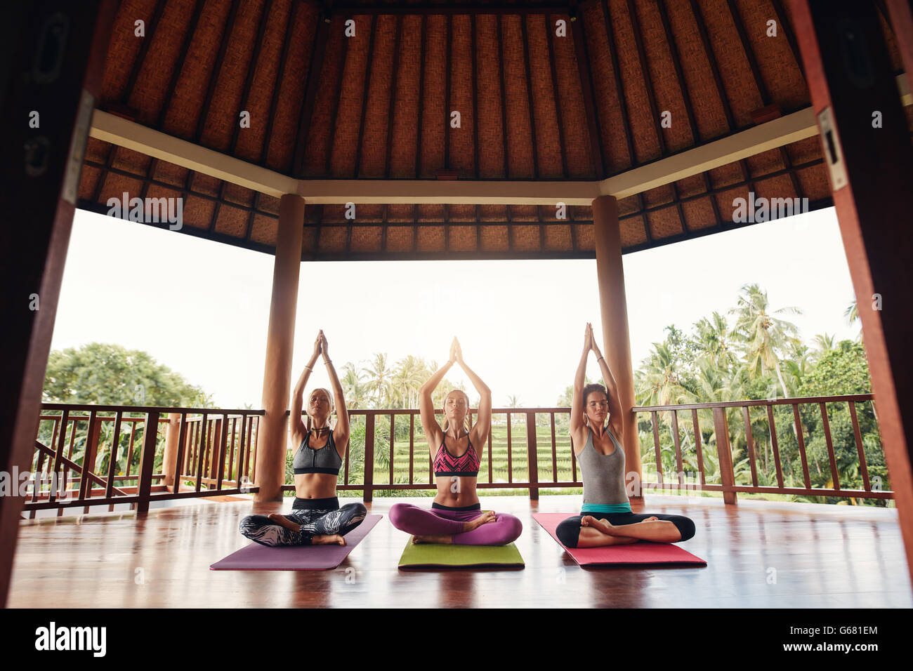 Three young women practicing yoga in a gym sitting cross legged on their mats and meditating. Group of people doing - Stock Image