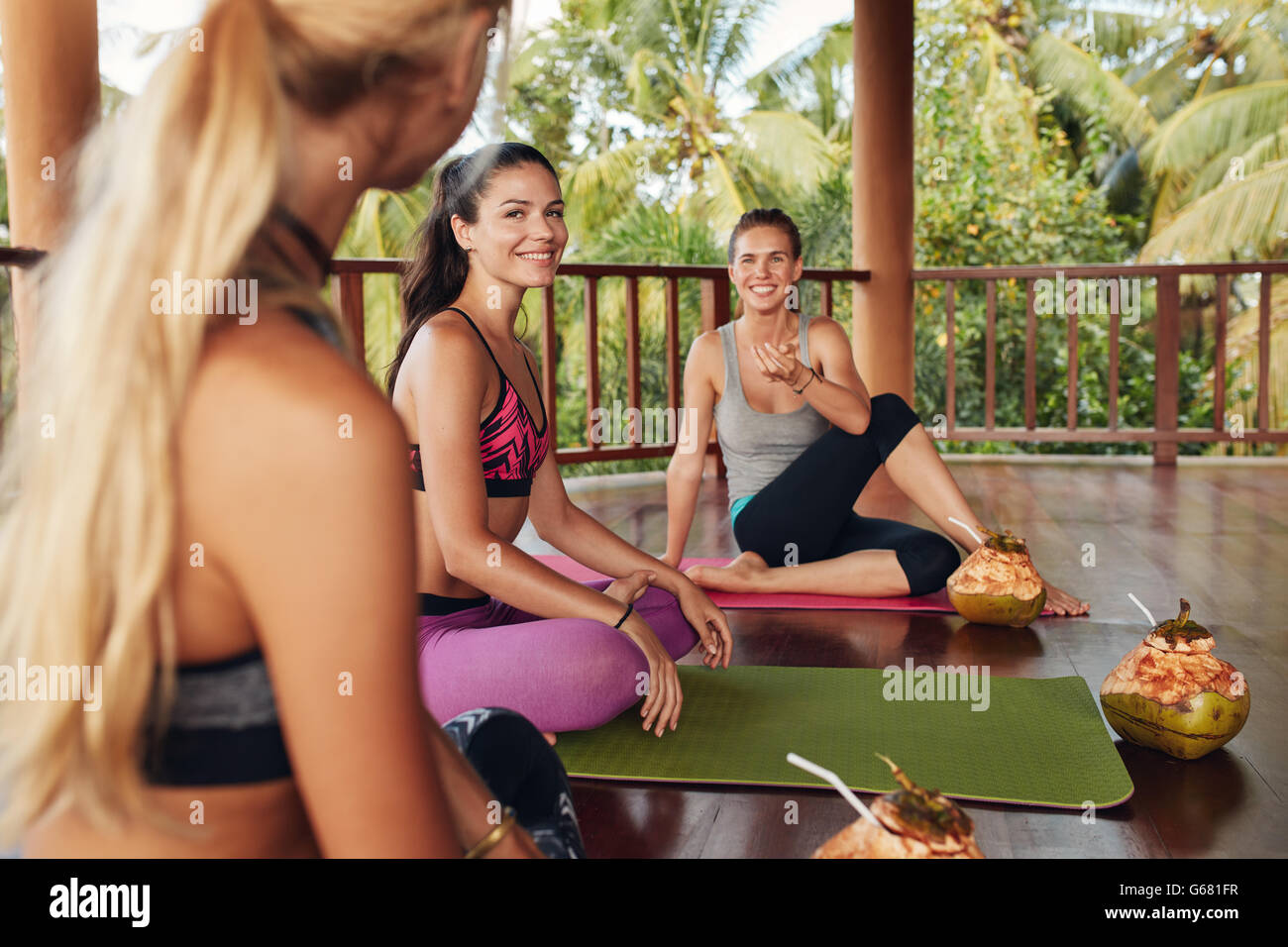 Group of women relaxing after yoga class. Three young women relaxing with coconut juice and talking after yoga session. - Stock Image