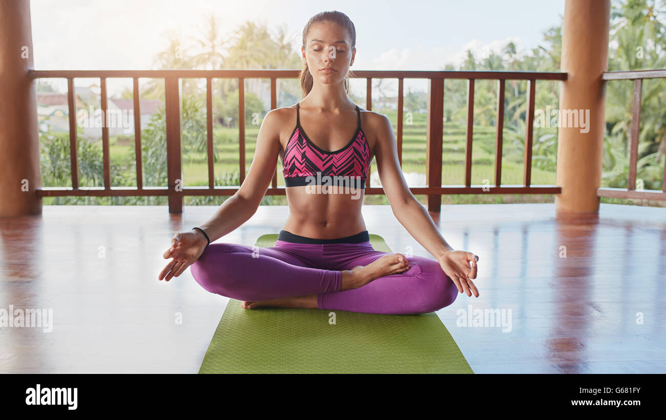 Shot of fit young woman meditating in lotus yoga pose at health center. Healthy young female practising yoga, she - Stock Image