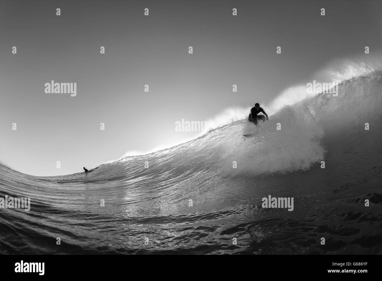 Surfer unidentified silhouetted surfing water action closeup swimming photo. - Stock Image