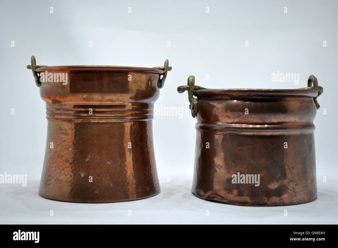 two shiny copper cauldrons with reflections - Stock Image