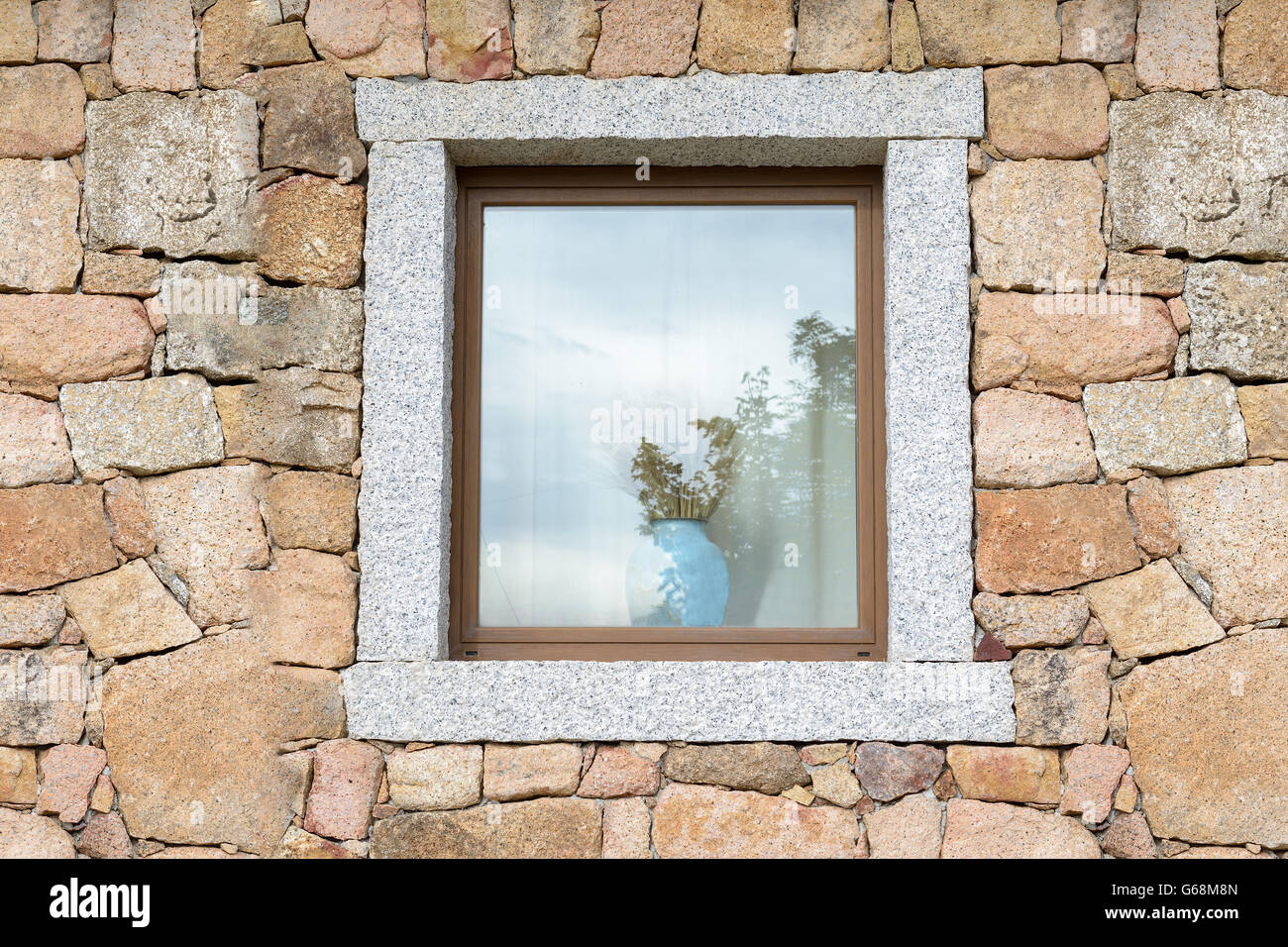 Open window on a block of granite wall with a vase of ears of corn. - Stock Image