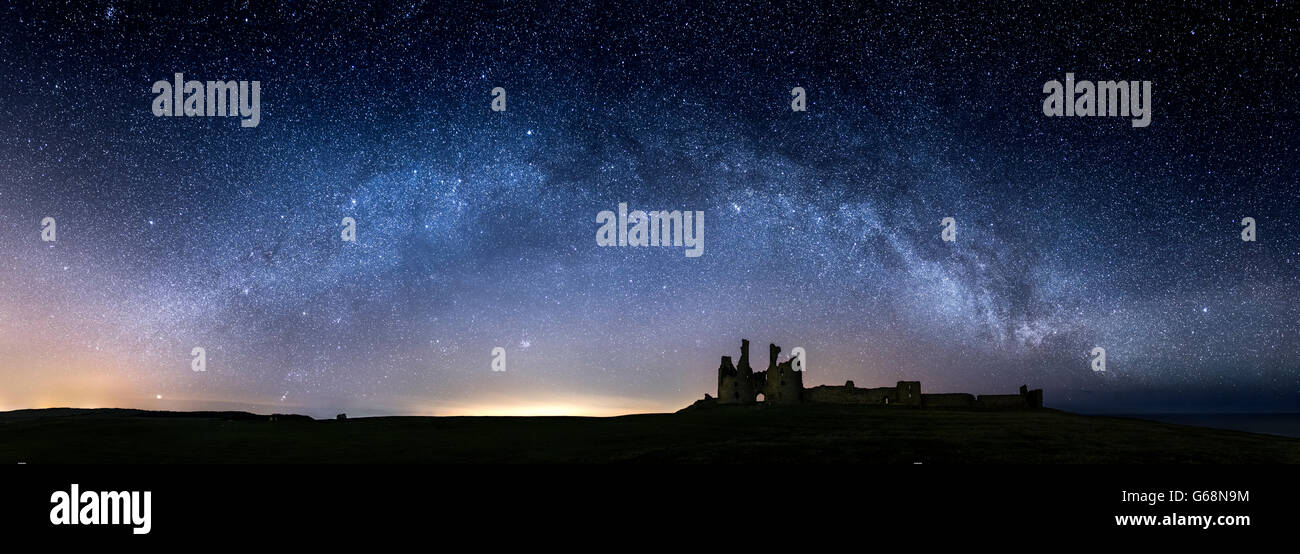 The Milky Way arcing over Dunstanburgh Castle in Northumberland UK - Stock Image