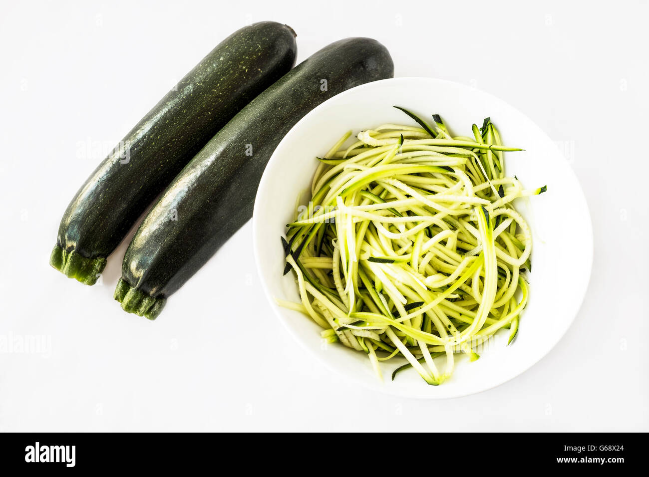 Two zucchini or courgettes with some spiralized for pasta substitute in a white bowl on white background Stock Photo