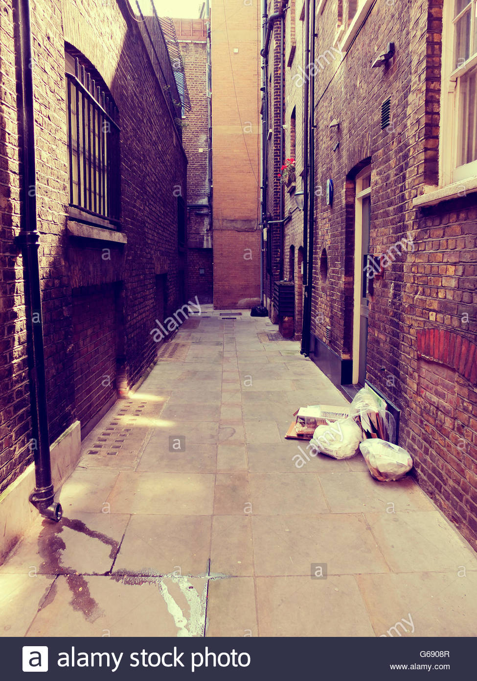 Dirty London alleyway with rubbish sacks - Stock Image