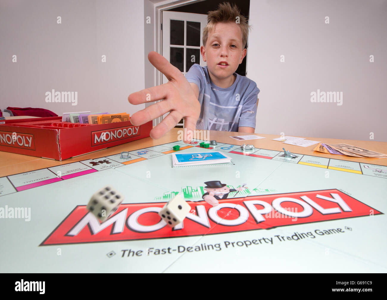 A boy playing the board game Monopoly - Stock Image