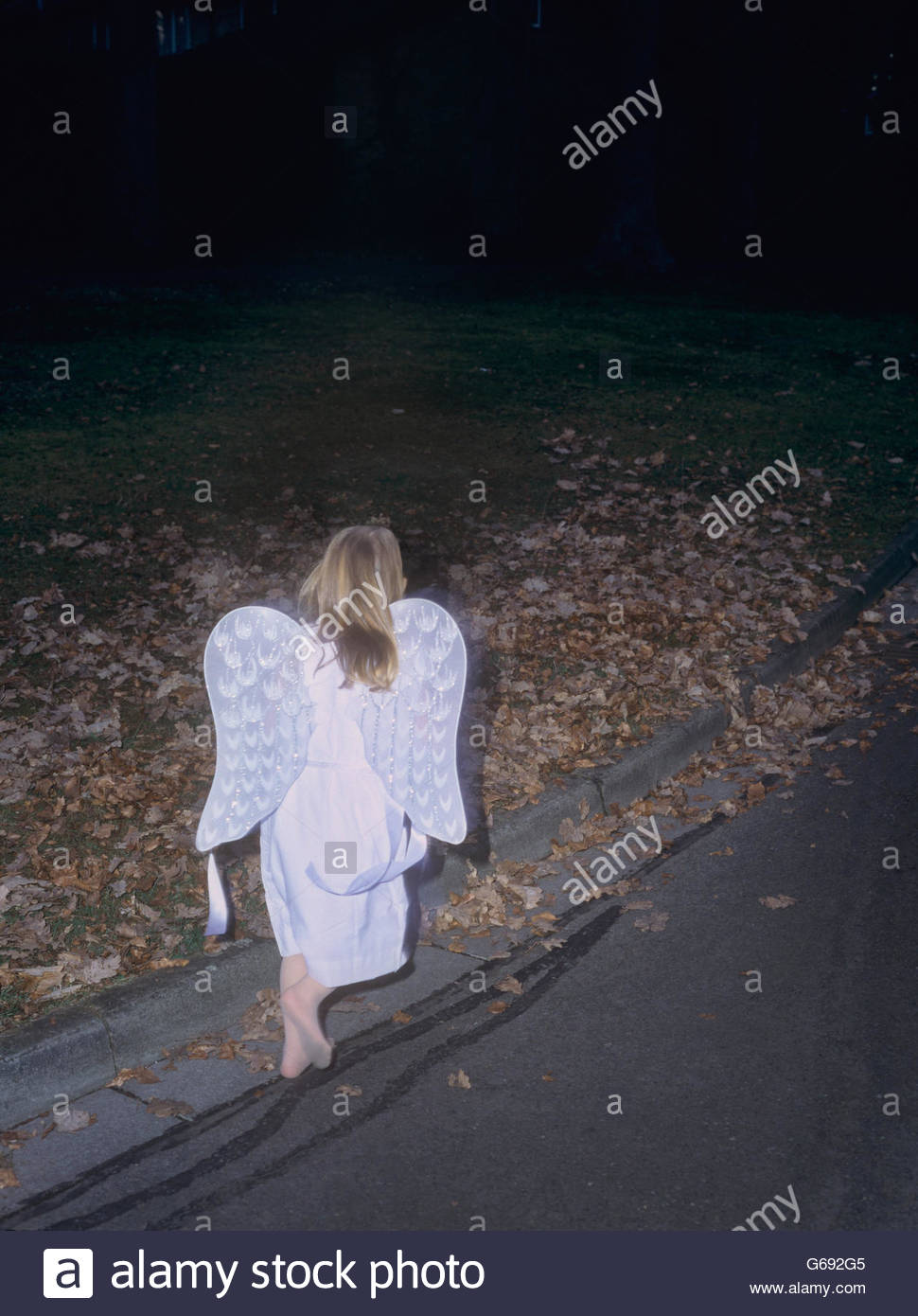 Young girl dressed as an angel walking barefooted (III) - Stock Image