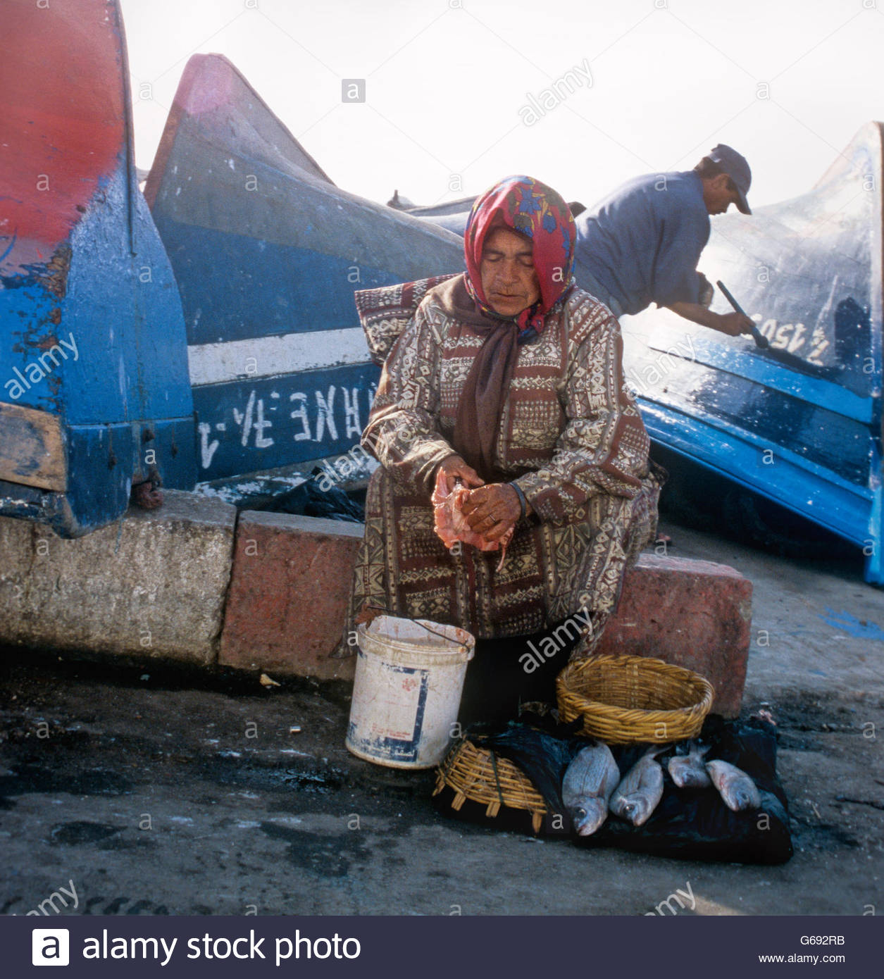 Old woman gutting fish over a bucket in a Moroccan harbour - Stock Image