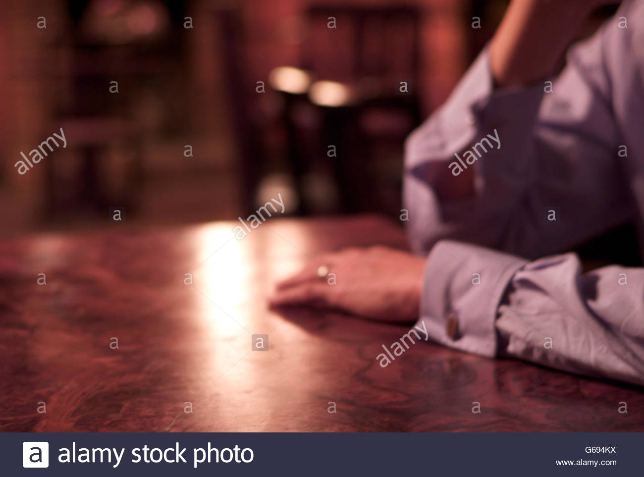 Man's hand lying on pub table with his wedding ring shining - Stock Image
