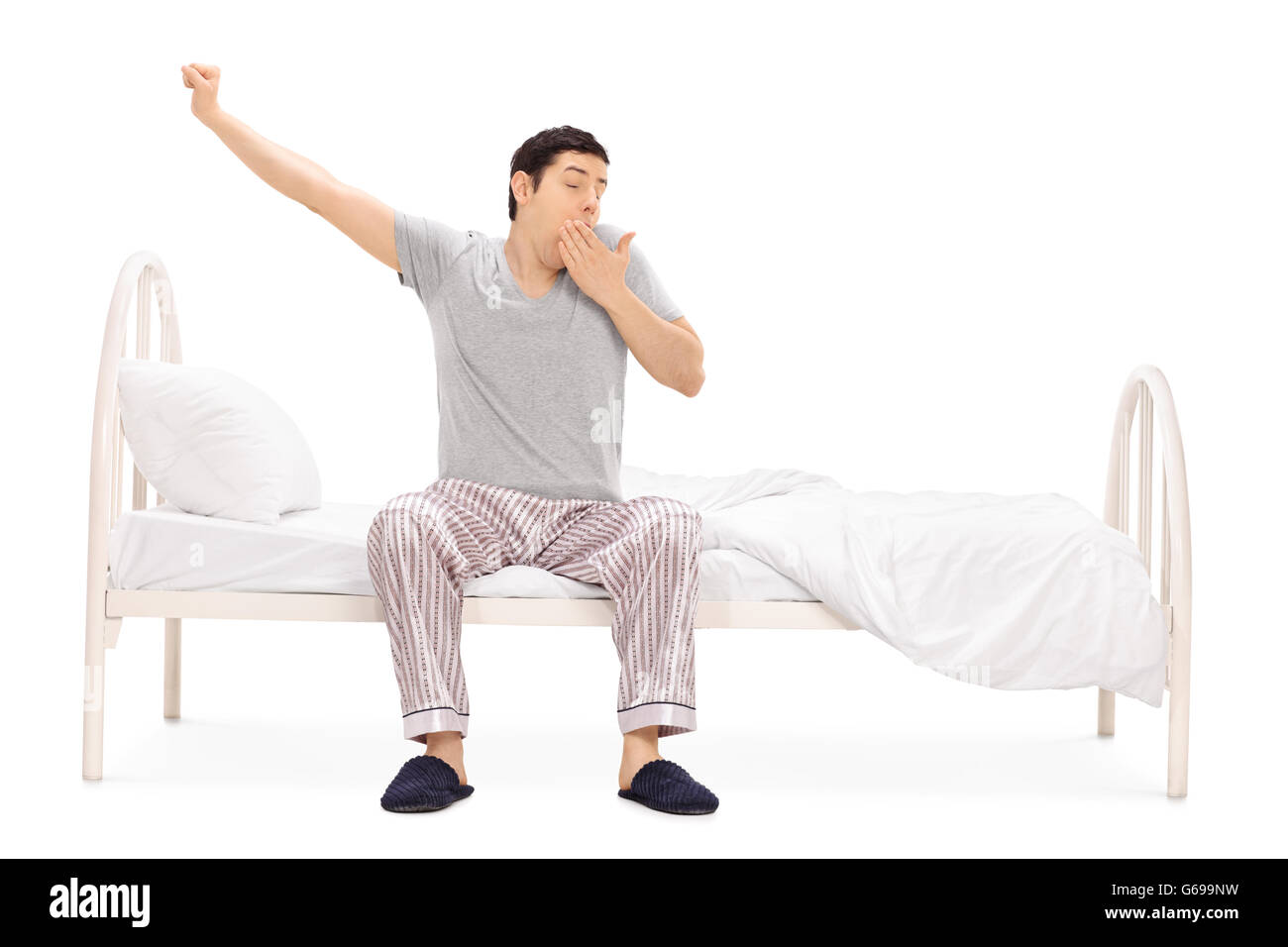 Young guy in pajamas sitting on a bed and yawning isolated on white background - Stock Image