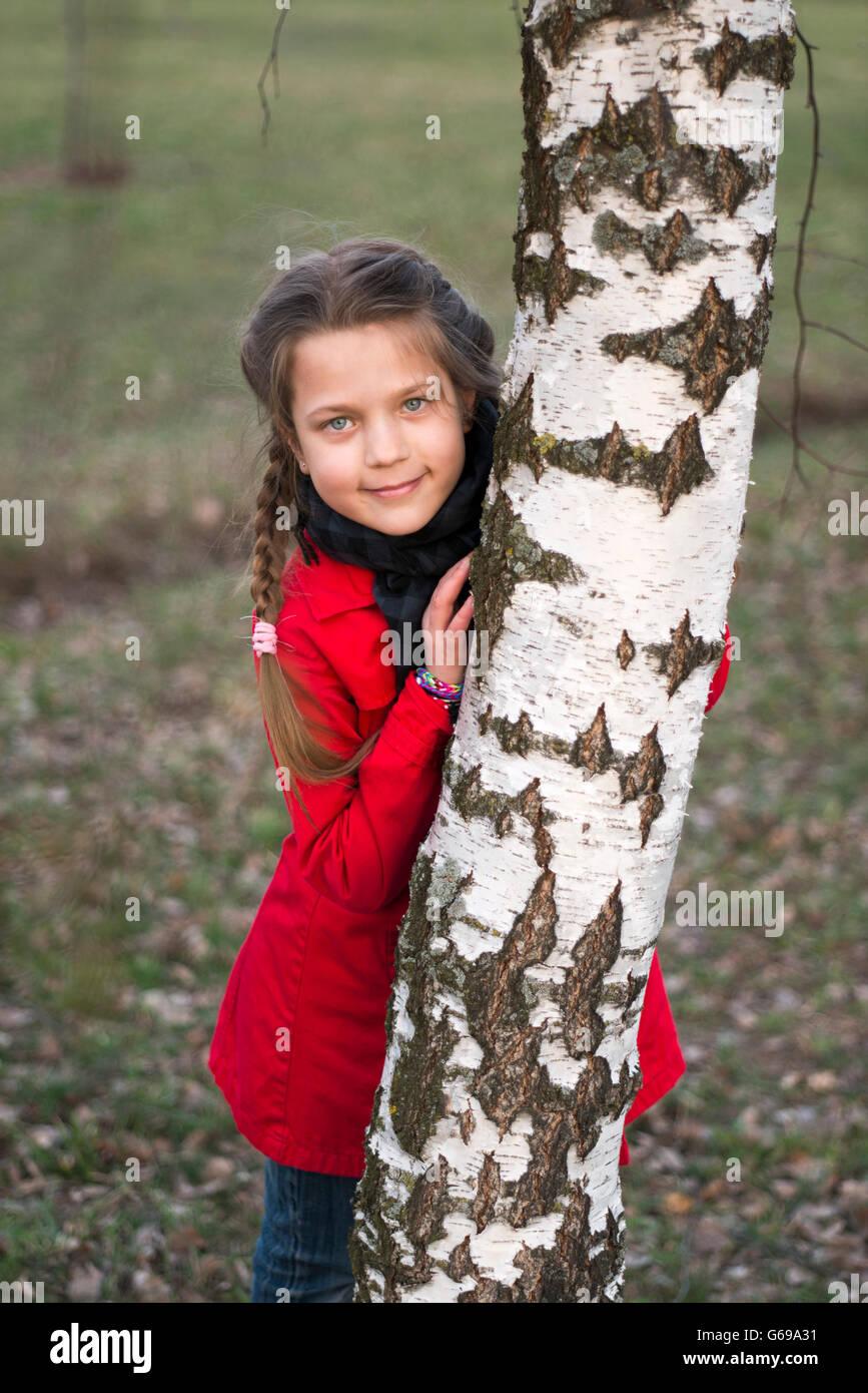 girl hidden behind birch tree stem - Stock Image