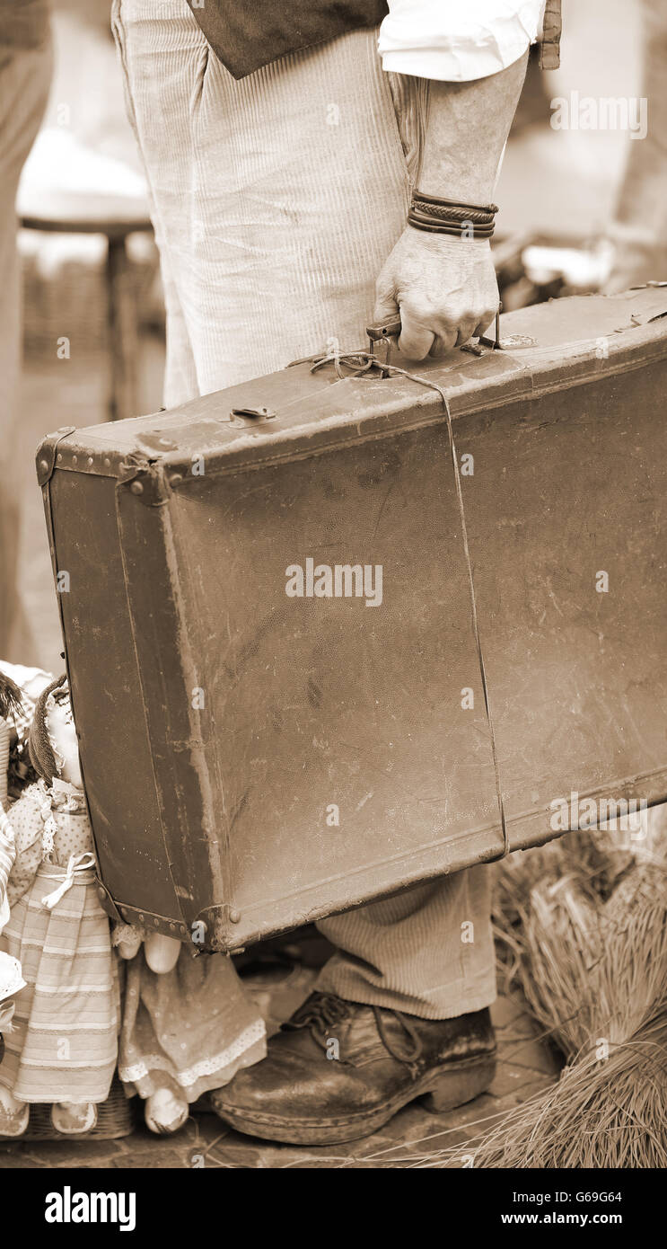 poor immigrant with old leather suitcase waiting to boarding sepia effect - Stock Image
