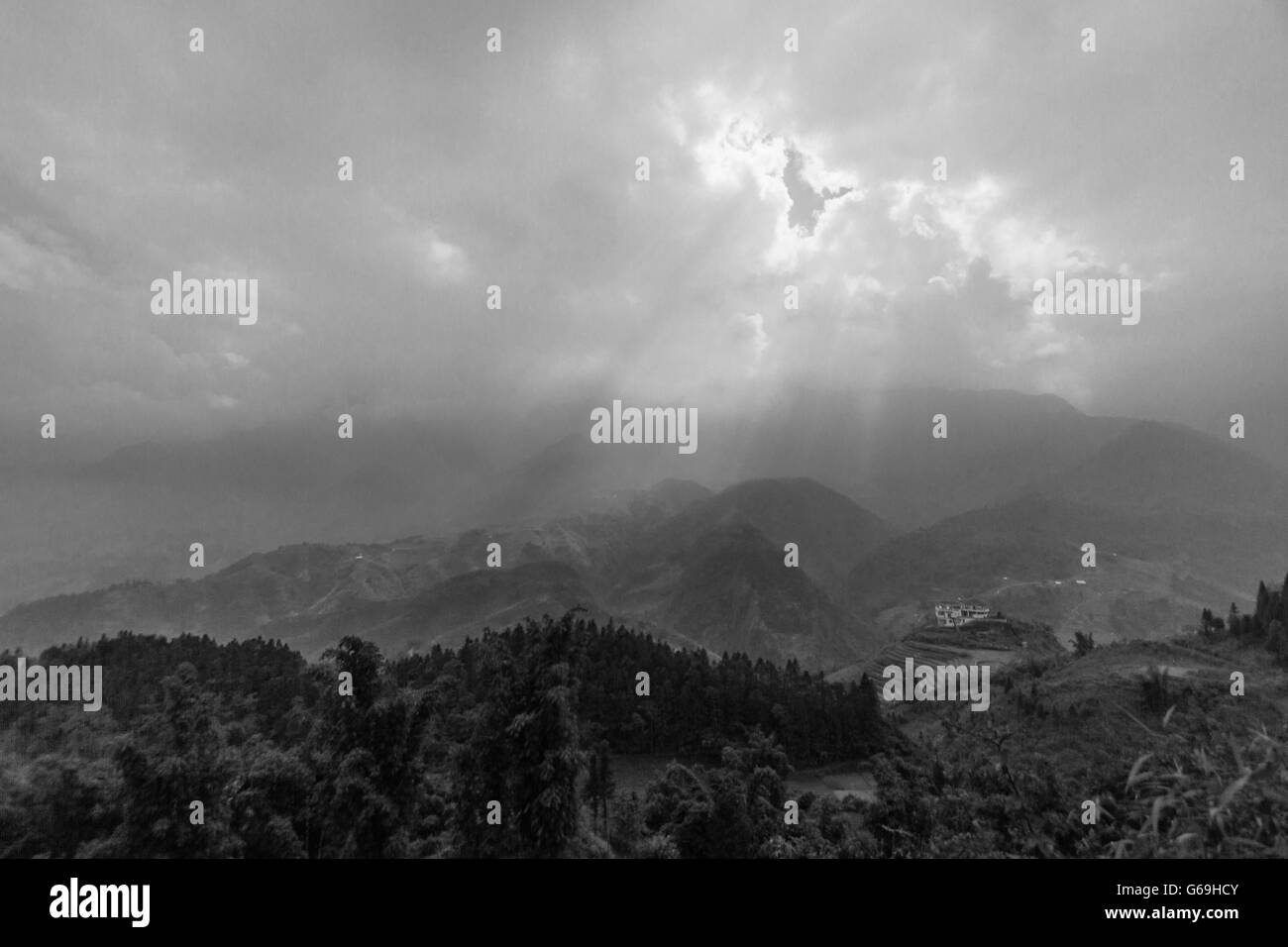 Lush vegetation, mountains and the sun breaking through a dense blanket of clouds in northern Vietnam. - Stock Image