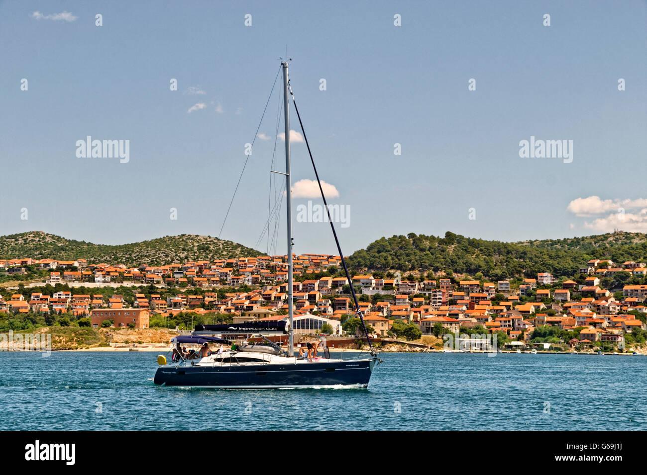 Cruising yacht motoring past Sibenik on the Cikola River, Dalmatia, Croatia. Stock Photo