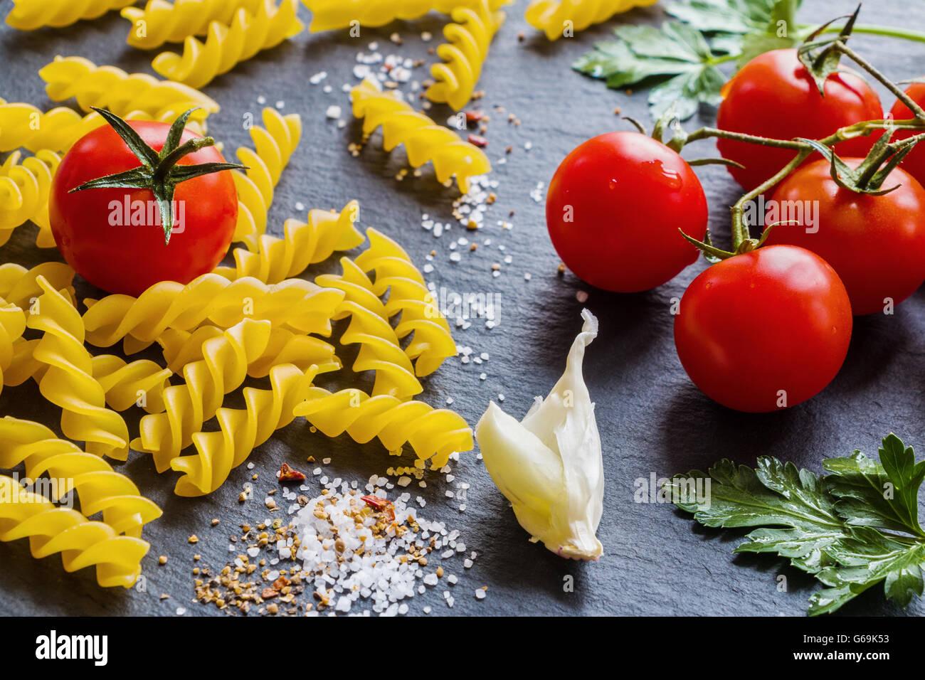Pasta ingredients (fusilli) on black slate background. - Stock Image