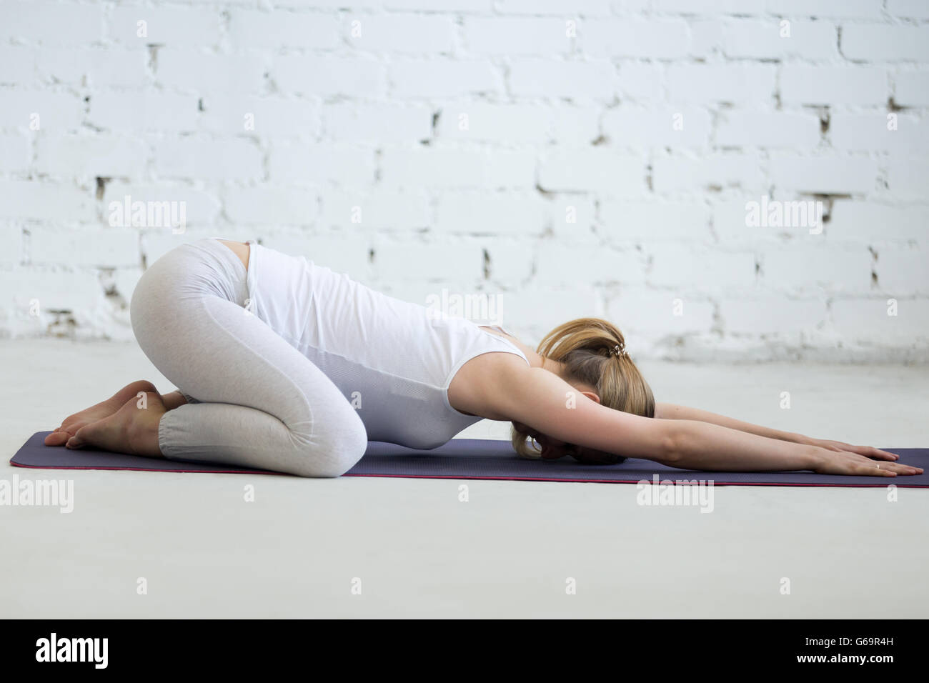 Pregnancy Yoga and Fitness. Portrait of young pregnant yoga model working out in loft with white walls. Pregnant - Stock Image