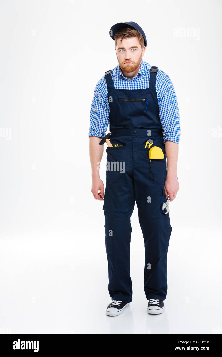 Full length of funny tired young reapairman in overall and cap - Stock Image