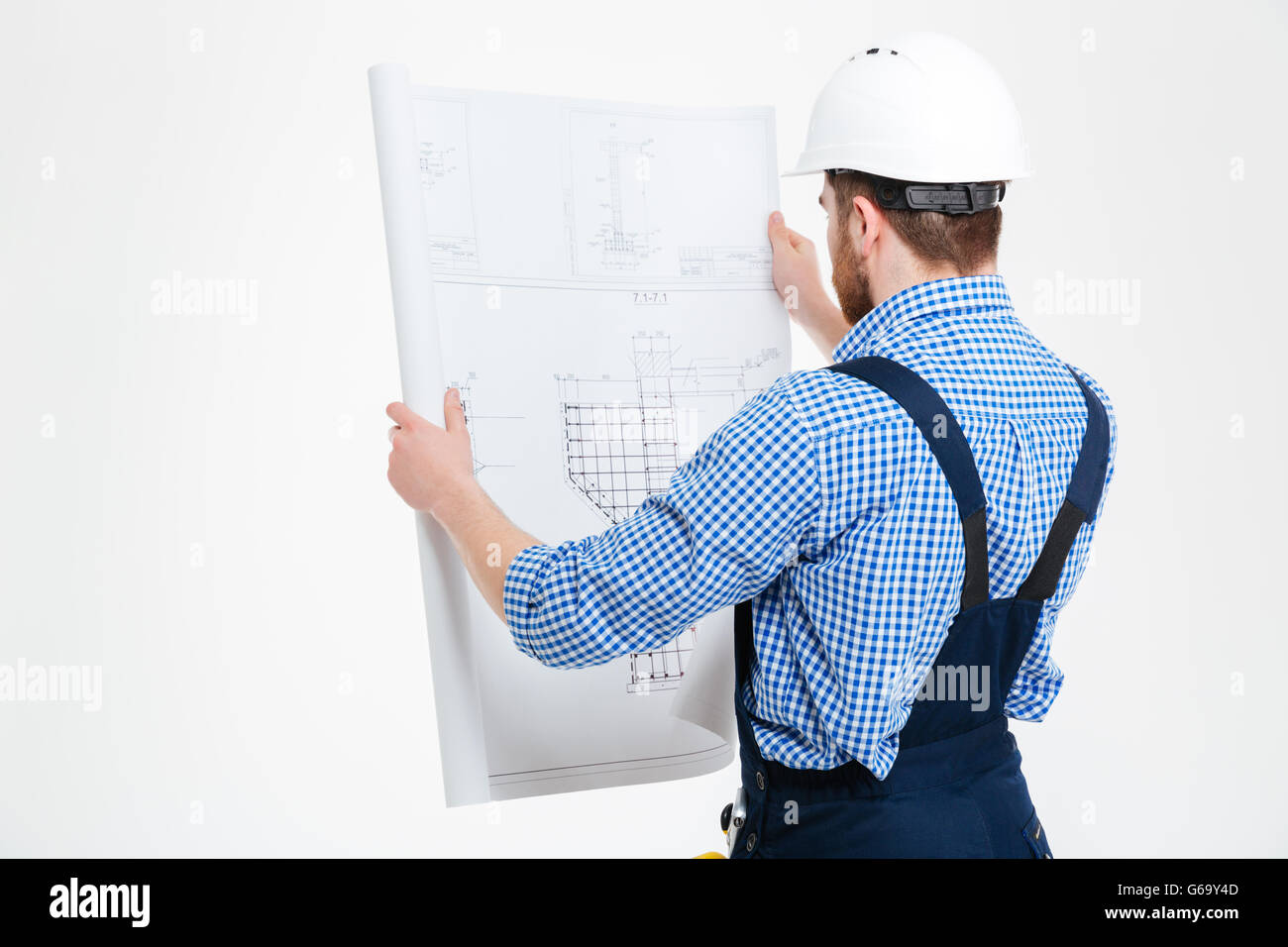 Back view of man builder in helmet working with blueprint - Stock Image