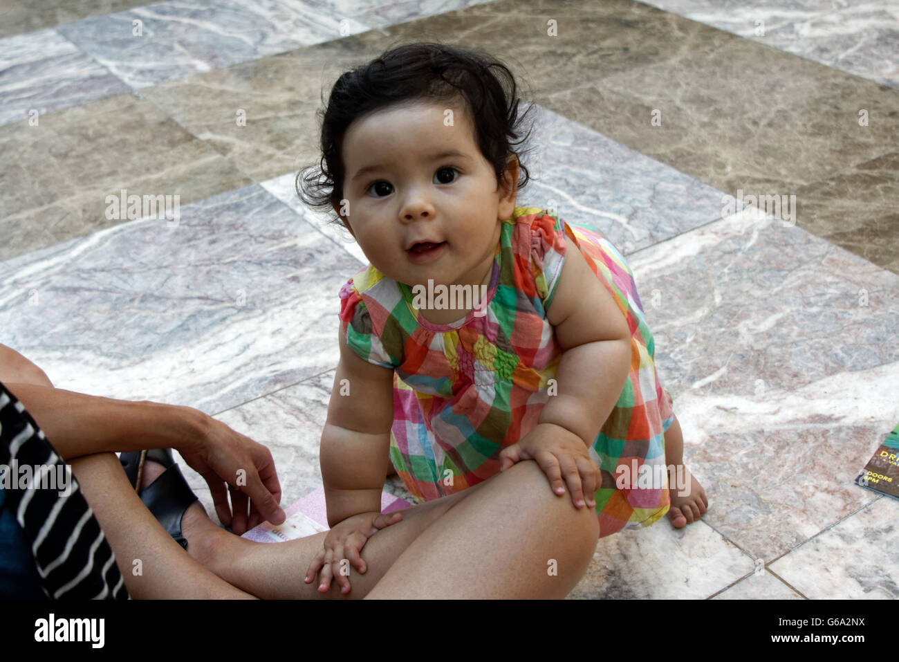 A baby attending a concert with her parents in Battery Park City, a neighborhood in Manhattan, New York City. - Stock Image