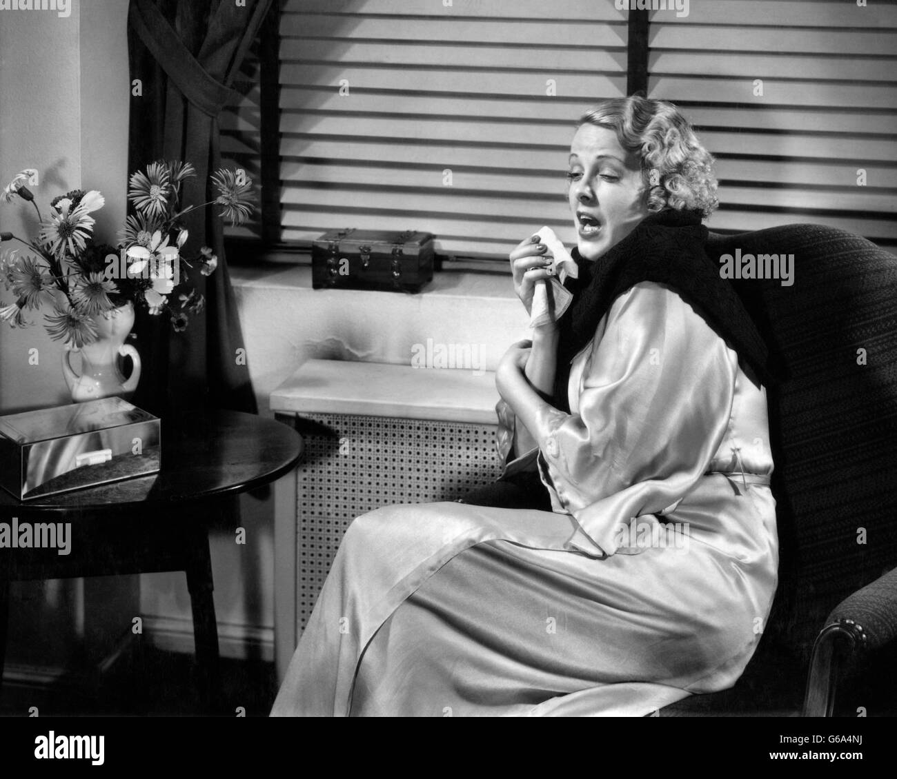 1930s WOMAN SNEEZING COUGHING WITH COLD SITTING NEXT TO RADIATOR FOR HEAT WARMTH - Stock Image