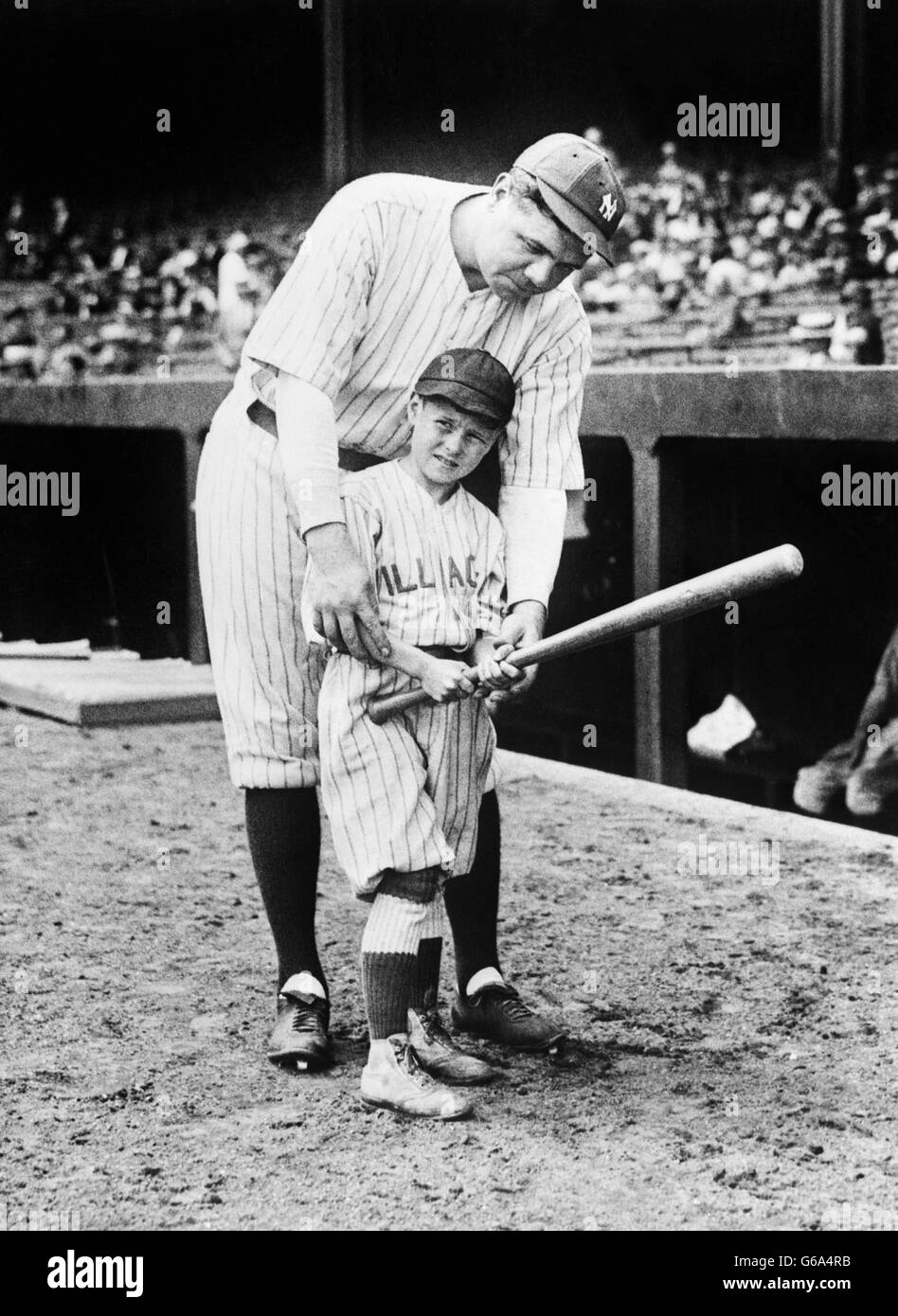 1930s BASEBALL PLAYER BABE RUTH COACHING YOUNG BOY HOW TO SWING BAT ON BASEBALL FIELD - Stock Image