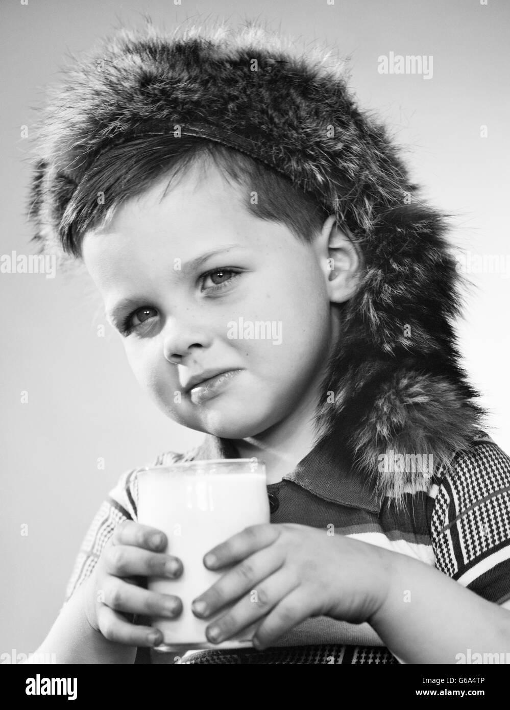 368d4e2eba8 1950s PORTRAIT BOY WEARING DAVY CROCKETT COONSKIN CAP HOLDING GLASS OF MILK  LOOKING AT CAMERA -