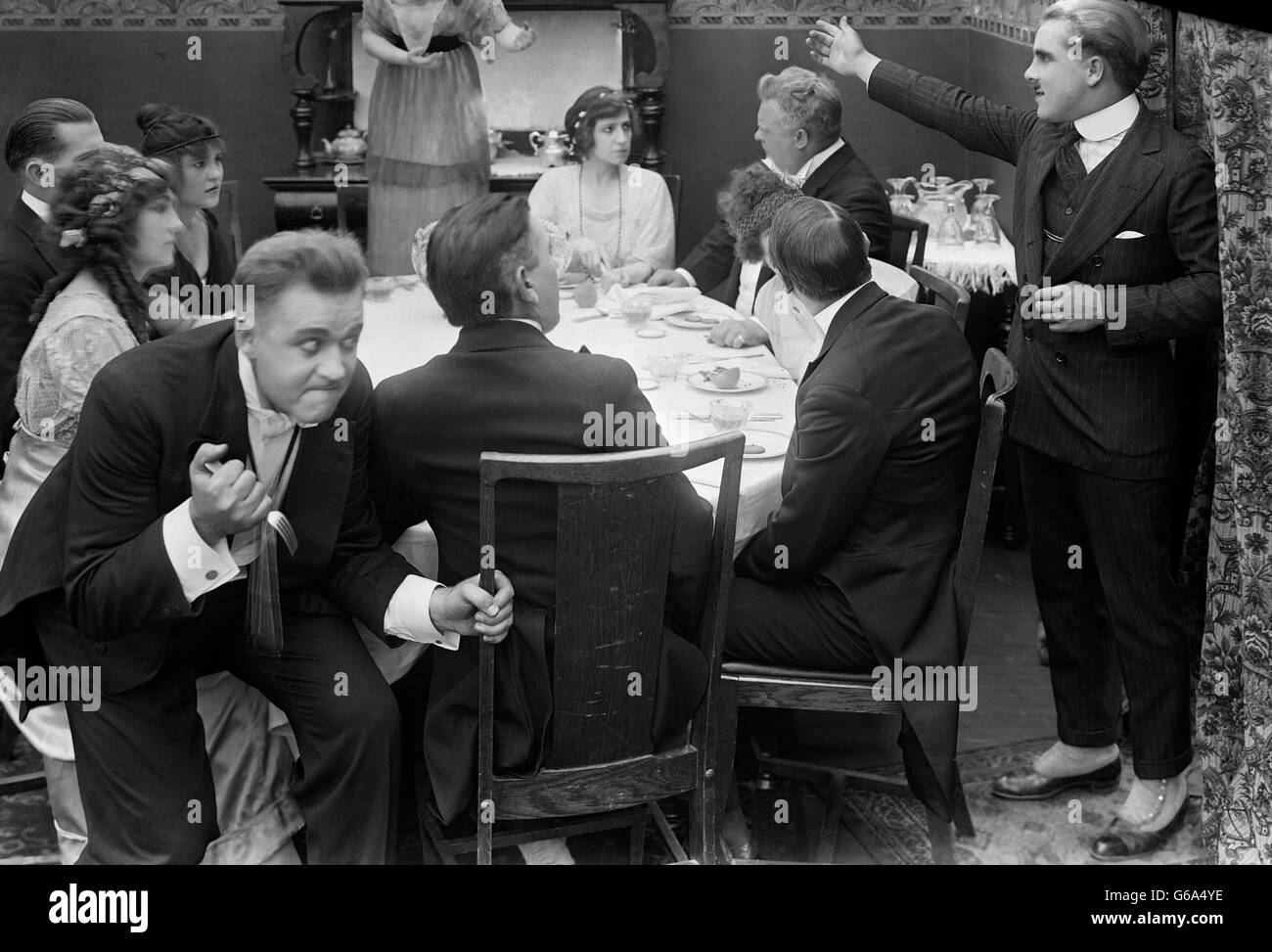1910s MAN CLUTCHING FORK SKULKING BEHIND GROUP AT DINNER TABLE SILENT MOVIE STILL - Stock Image