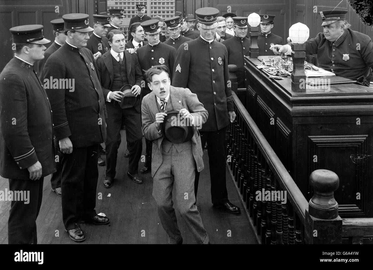1910s 1920s MAN CRINGING BEFORE POLICE DESK SERGEANT POINTING FINGER ACCUSINGLY SILENT MOVIE STILL - Stock Image