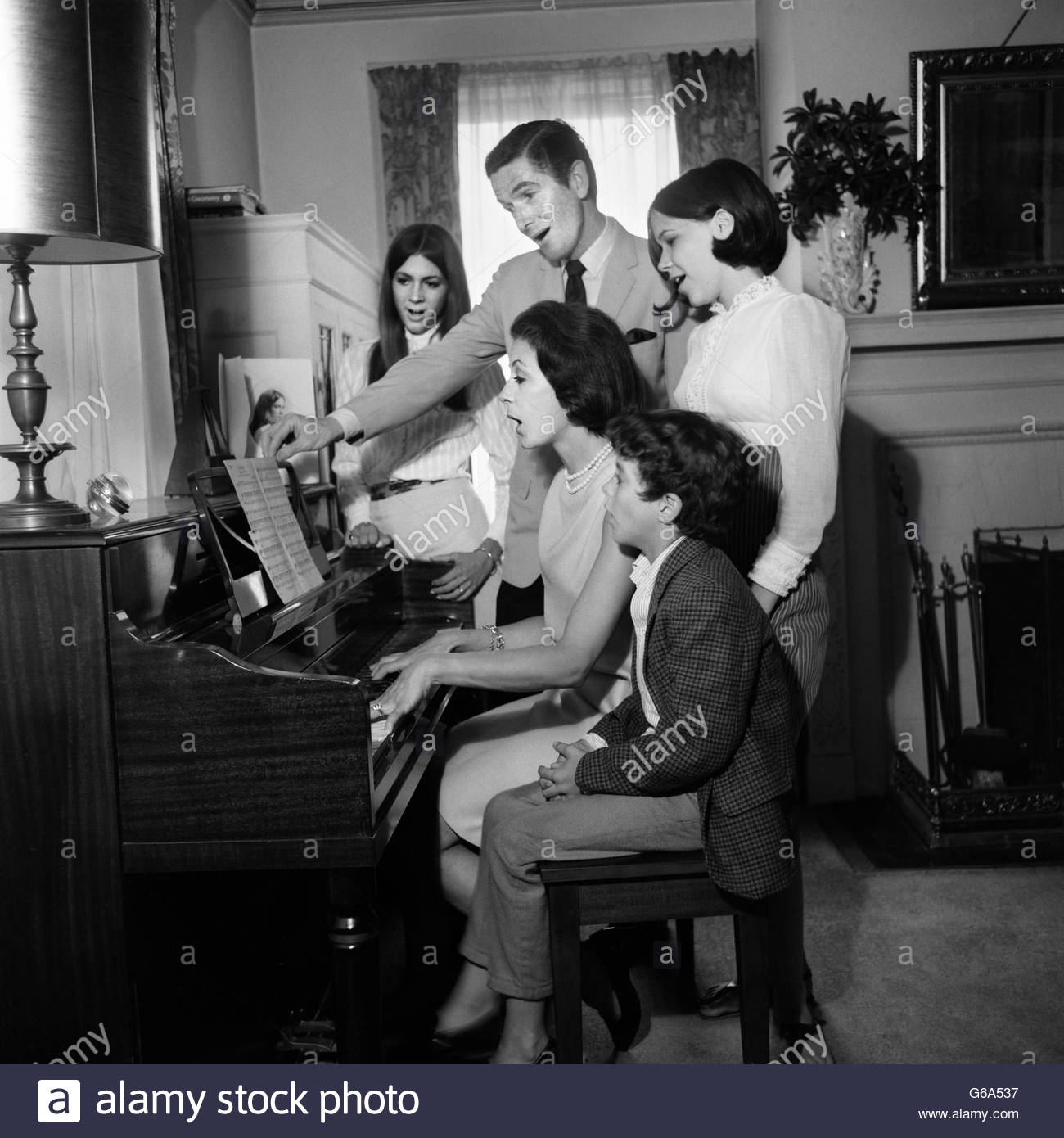 1960s FAMILY 5 FATHER CHILDREN SINGING AROUND PIANO PLAYED BY MOTHER - Stock Image