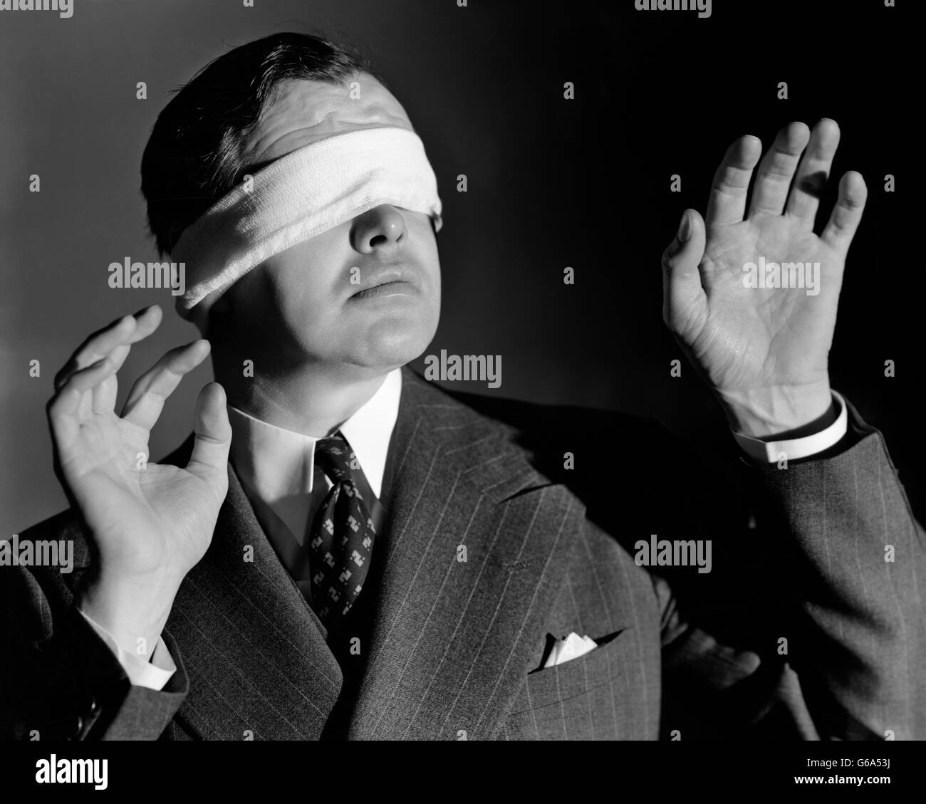 1930s 1940s BUSINESSMAN WEARING BLINDFOLD REACHING FORWARD WITH HANDS - Stock Image