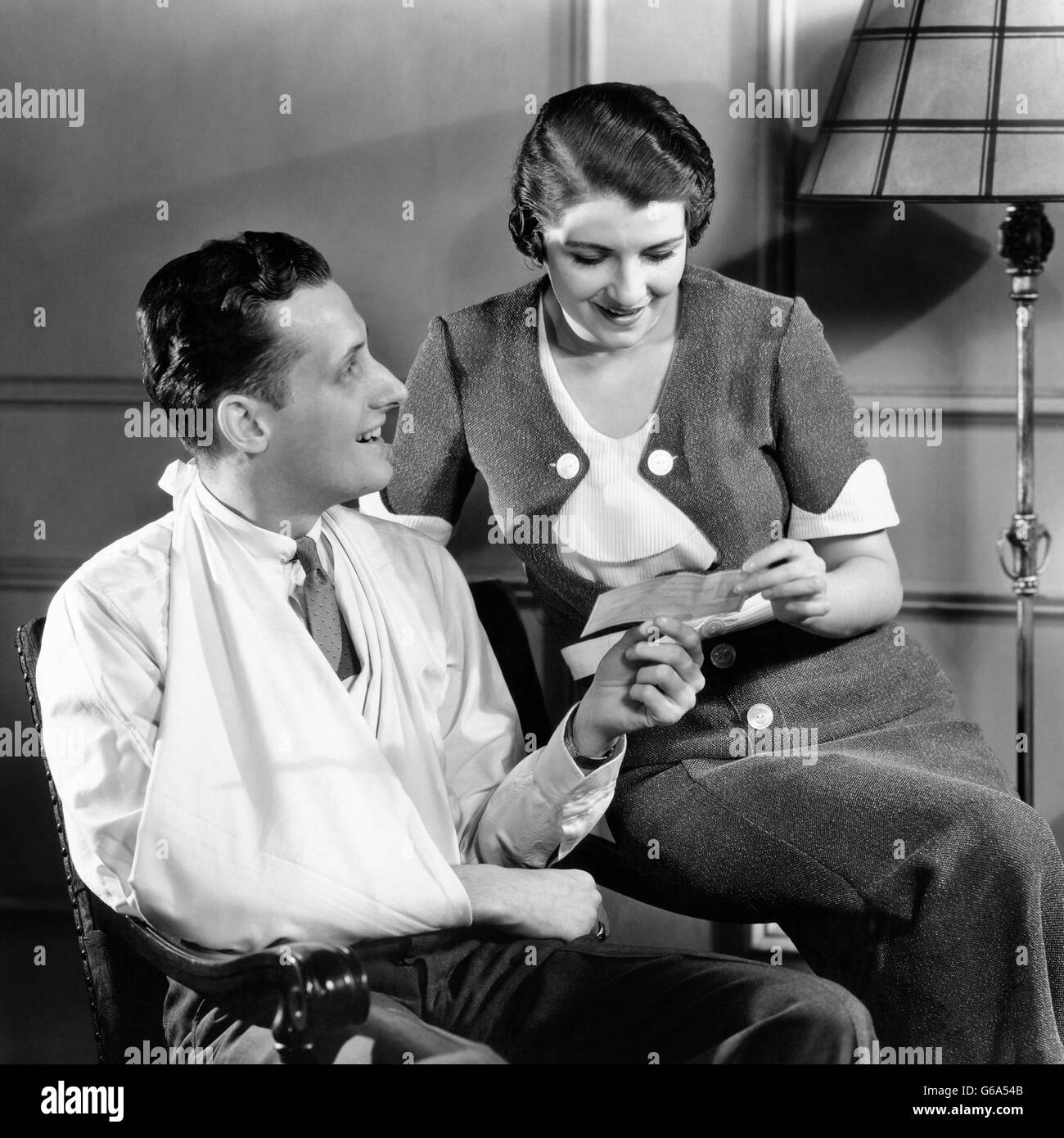 1930s COUPLE WOMAN HOLDING INSURANCE CHECK MAN WITH INJURED ARM IN SLING - Stock Image
