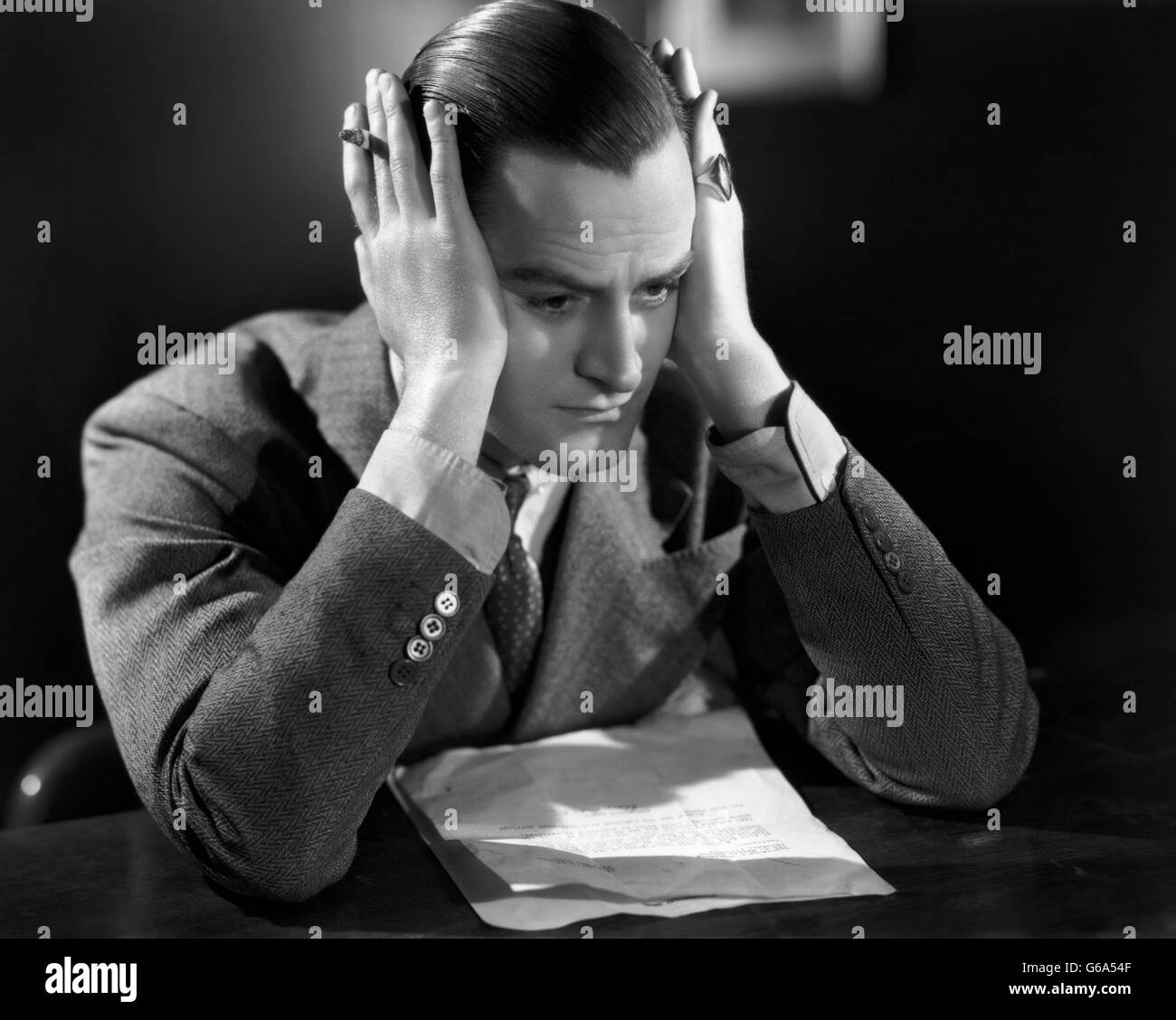 1930s DEPRESSED BUSINESS MAN HOLDING HEAD UP WITH HIS HANDS OVER HIS EARS - Stock Image