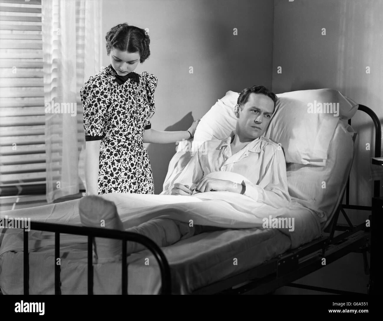 1930s WOMAN BY BEDSIDE MAN IN HOSPITAL BED DEPRESSED WITH BANDAGED LEG - Stock Image