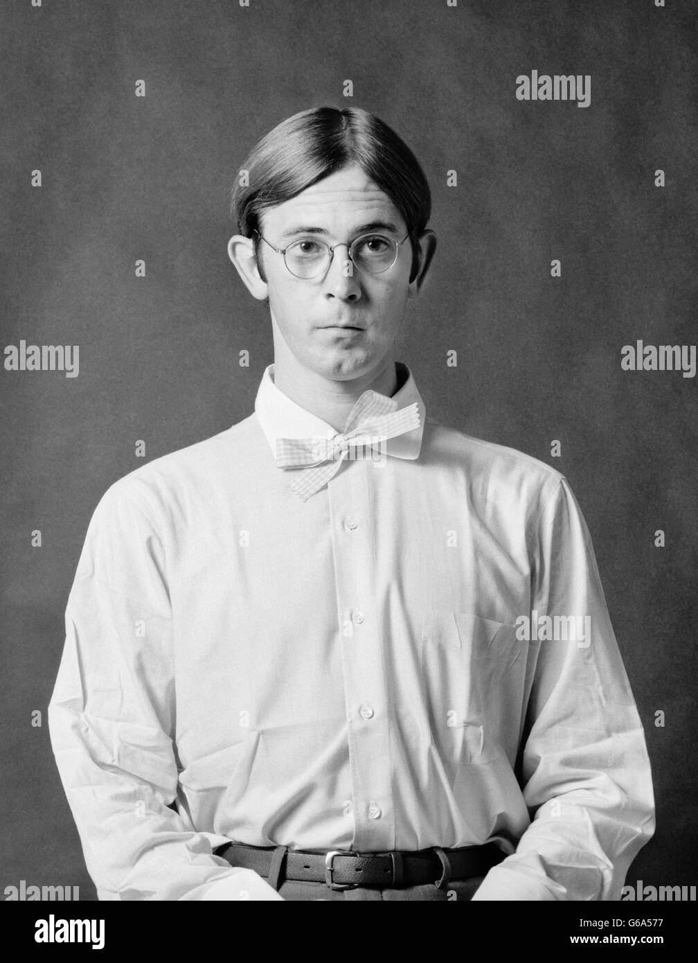 1970s PORTRAIT GEEKY DORKY SHY WALLFLOWER YOUNG MAN WEARING SPECTACLES WHITE SHIRT AND BOW TIE - Stock Image
