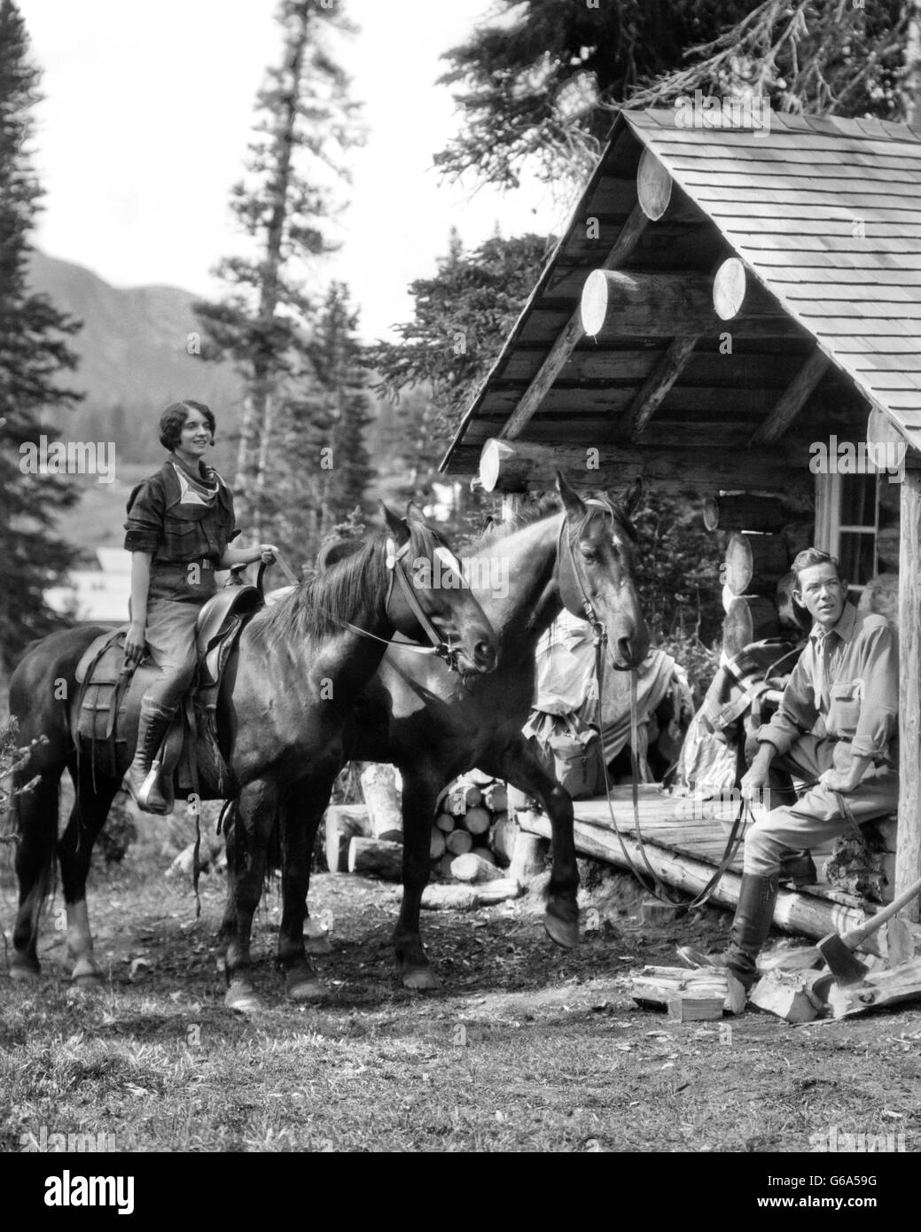 1930s COUPLE IN FRONT OF LOG CABIN WOMAN ON HORSE MAN SITTING ON PORCH HOLDING REINS OF SECOND HORSE ASSINIBOINE - Stock Image