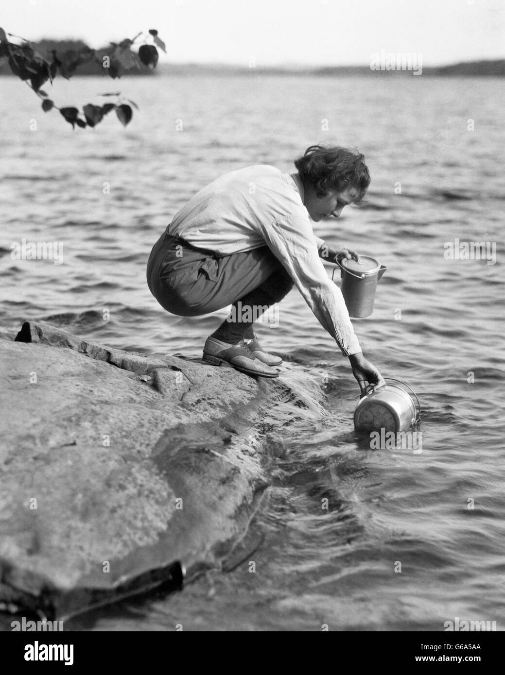 1920s 1930s WOMAN CAMPING CROUCHING ON ROCK FILLING METAL BUCKET WITH WATER FROM LAKE - Stock Image