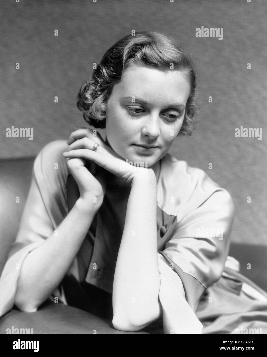1930s PORTRAIT PENSIVE WOMAN SITTING IN CHAIR LEANING CHIN ON HAND THINKING - Stock Image